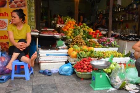 frutas vietnam hanoi mercado de rua vendedora pé para o alto rambutam
