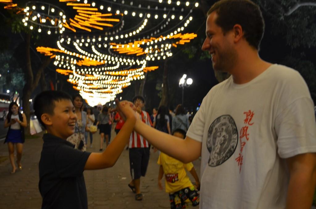 menino vietnamita homem brasileiro encontro aperto de mãos